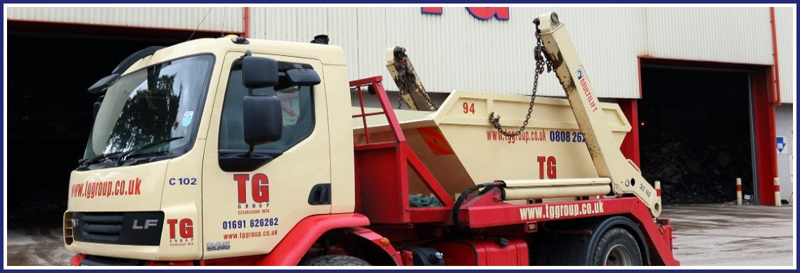 TG Skip Hire delivery lorry with chain load skip